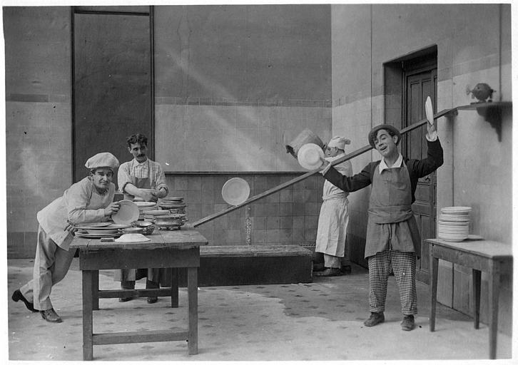 Rémond Frau qui interprète Dandy dans une cuisine jouant avec des assiettes en présence de trois hommes dont Zaté dans un épisode de 'Dandy' de Georges Rémond