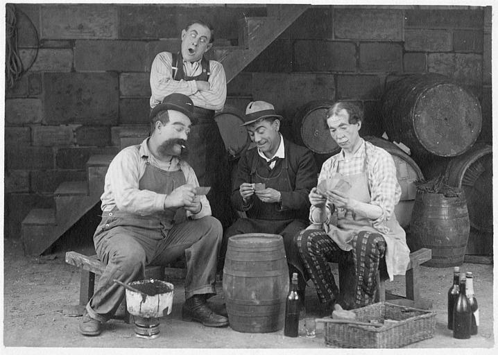 Dans une cave, Rémond Frau qui interprète Dandy joue aux cartes sur un tonneau avec Max, Louis et Ulysse dans un épisode de 'Dandy' de Georges Rémond