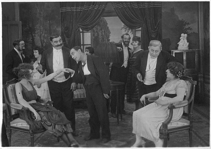 Dans un salon, Rémond Frau qui interprète Dandy joue le galant en tenant la main d'une femme assise tout en étant entouré de plusieurs personnages dans un épisode de 'Dandy' de Georges Rémond