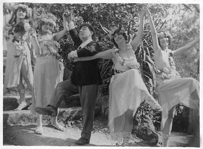 Dans un escalier de jardin, Rémond Frau dans le rôle de Dandy est dans une farandole entouré de femmes portant des colliers de fleurs dans un épisode de 'Dandy' de Georges Rémond