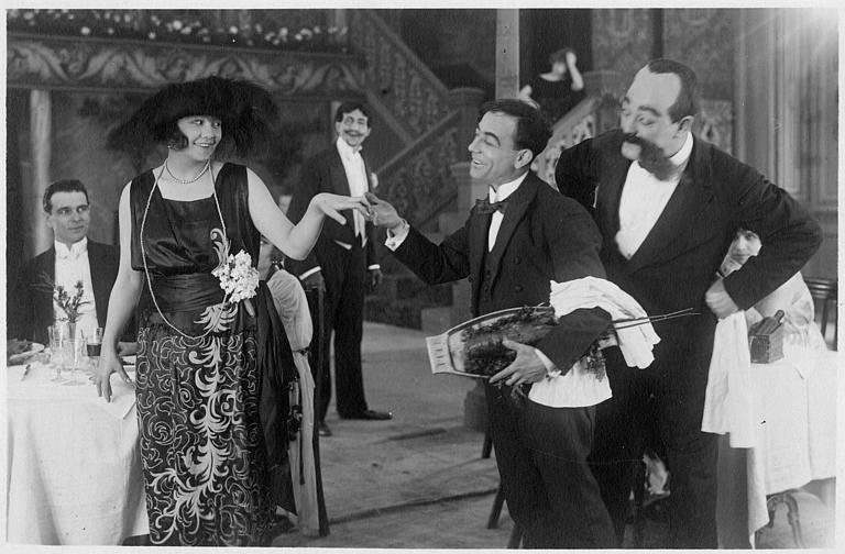 Rémond Frau dans le rôle de Dandy en serveur, un homard sous le bras, joue au galant en prenant la main de Florelle sous l'oeil de Max et Smote dans un épisode de 'Dandy' de Georges Rémond