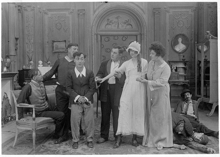 Dans un salon, Rémond Frau dans le rôle de Dandy, est timide devant Pansy Wilde qu'on lui présente entourée de et plusieurs personnages Madame Devries, Smote, Riche, Gaston, Max, Brenie et Gohier dans 'Dandy-afficheur' de Georges Rémond