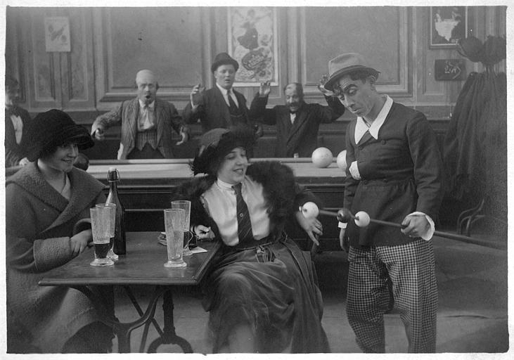 Rémond Frau dans le rôle de Dandy amuse deux femmes attablées en présence des autres joueurs dans un épisode de 'Dandy' de Georges Rémond