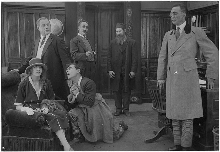 Rémond Frau dans le rôle de Dandy suppliant Lulu Legrand assise dans un fauteuil devant Max, Foottitt, Adolphe et Gaston  dans un épisode de 'Dandy' de Georges Rémond