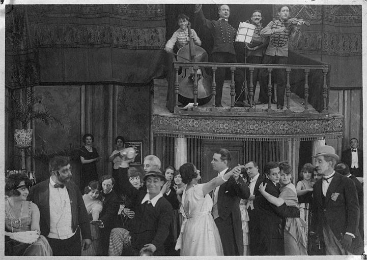 Dans une salle de bal, un orchestre fait danser le public : Rémond Frau dans le rôle de Dandy, Max, Foche et Smote dans un épisode de 'Dandy' de Georges Rémond