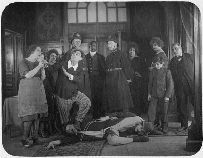 Rémond Frau dans le rôle de Dandy entouré par plusieurs personnages avec Max et Aimos, hommes ligotés à terre dans 'Dandy a des visions' de Georges Rémond
