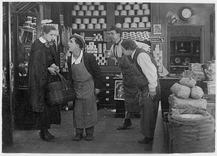 Rémond Frau dans le rôle de Dandy planté au milieu d'une épicerie avec Pollos, Germaine Cottin et Max l'entourant dans un épisode de 'Dandy' de Georges Rémond