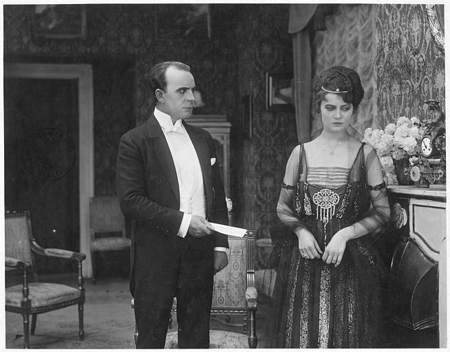 Dans un salon, Viggo Larsen tendant un papier à Grita von Ryt qui l'ignore dans 'Rote Spuren' de Viggo Larsen
