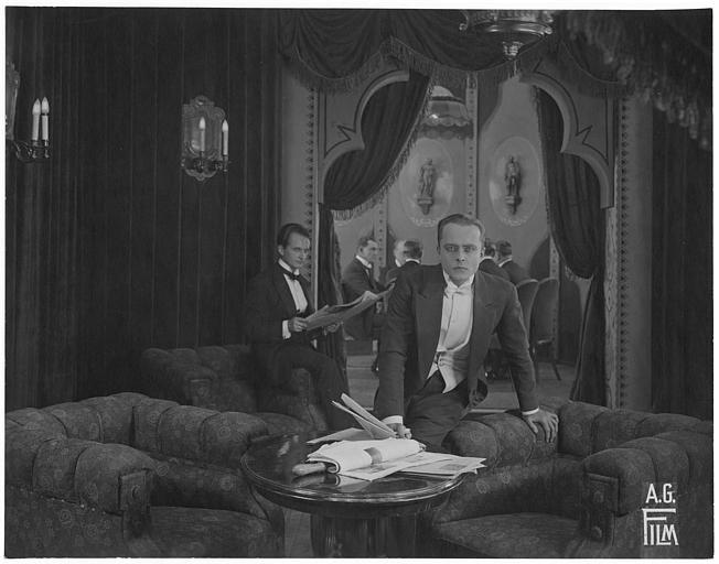 Ernst Hofmann réfléchissant, assis sur l'accoudoir d'un fauteuil, épié par un homme lisant le journal dans 'Kinder von Heute' d'Arthur Günsburg (A.G. Film)