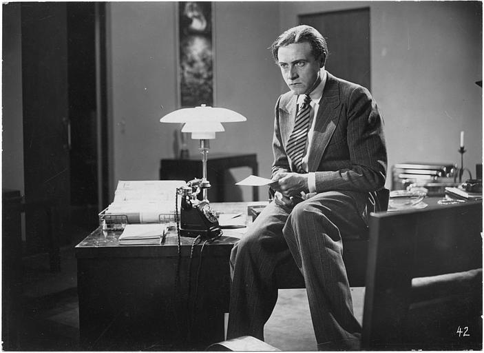 Willy Fritsch interprète Wolf Helius assis sur son bureau lisant un papier dans 'Frau im Mond' de Fritz Lang (Universum-Film A.G )