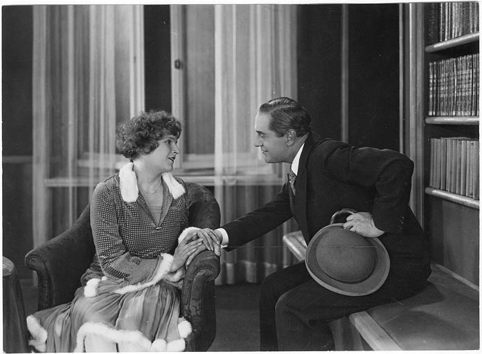 Dans une bibliothèque, une femme tient la main d'Harry Liedtke