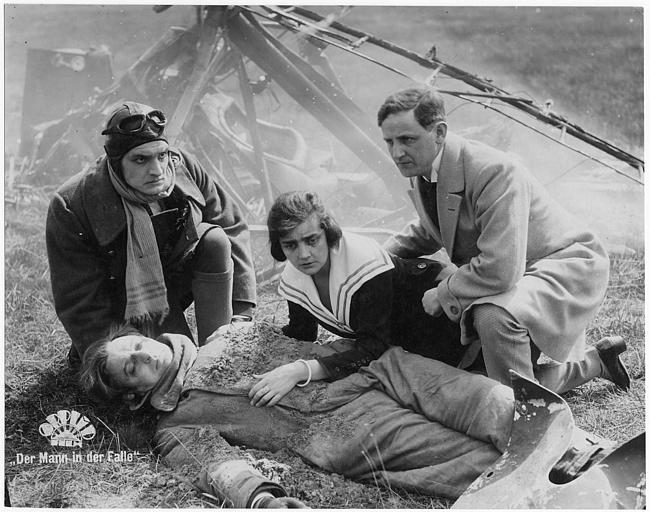 Suite à un accident d'avion, un homme au sol entouré de trois personnages à genoux : Sybill Morel est la fille du président, Harry Franck le Détective Morten et Ernst Dernburg interprète Pierre Roudnice dans 'Der mann in der Falle' de Wolfgang Neff (Orplid Film)