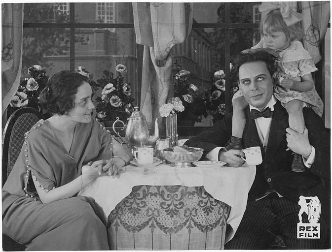 A table, Bernd Aldor porte une enfant sur ses épaules tandis que Sybill Morel lui sourit (Rex Film)