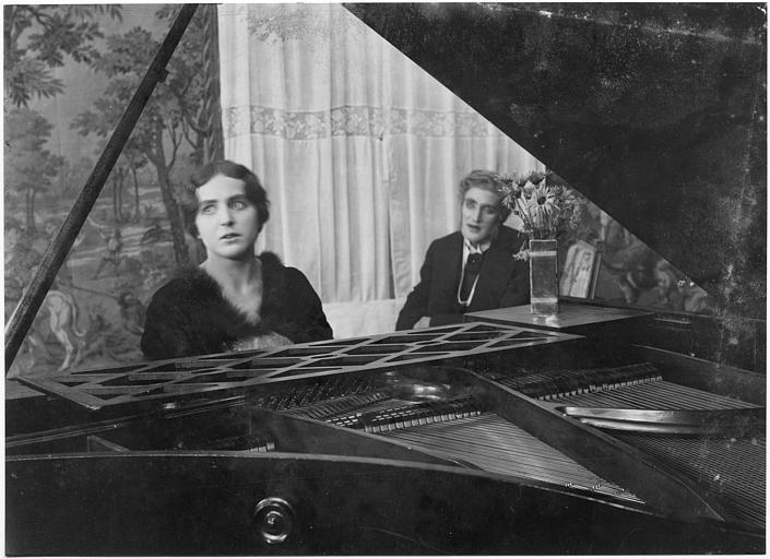 Hella Moja au piano avec un homme en arrière plan