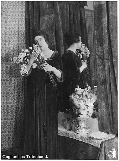 Dos au miroir, Martha Novelly respire un bouquet de fleurs dans 'Cagliostros Totenhand' de Nils Chrisander (Deutsche Bioscop Gmbh)