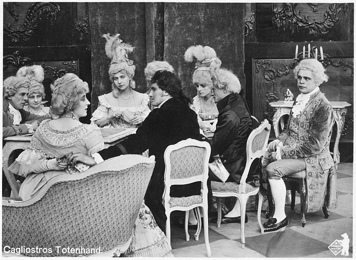 Personnages en costumes dont Martha Novelly jouant aux cartes autour d'une table dans 'Cagliostros Totenhand' de Nils Chrisander (Deutsche Bioscop Gmbh)