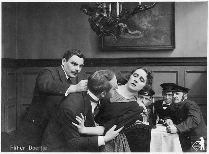 Dans un café, une femme tente de se défaire d'un homme qui l'étreint alors qu'un troisième cherche à les séparer : Martha Novelly et Rudolf Klein-Rogge dans 'Flitter-Döertje' de Robert Leffler (Deutsche Bioscop Gmbh)