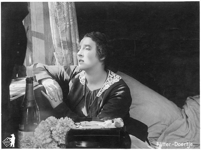 Martha Novelly assise devant une fenêtre dans 'Flitter-Döertje' de Robert Leffler (Deutsche Bioscop Gmbh)
