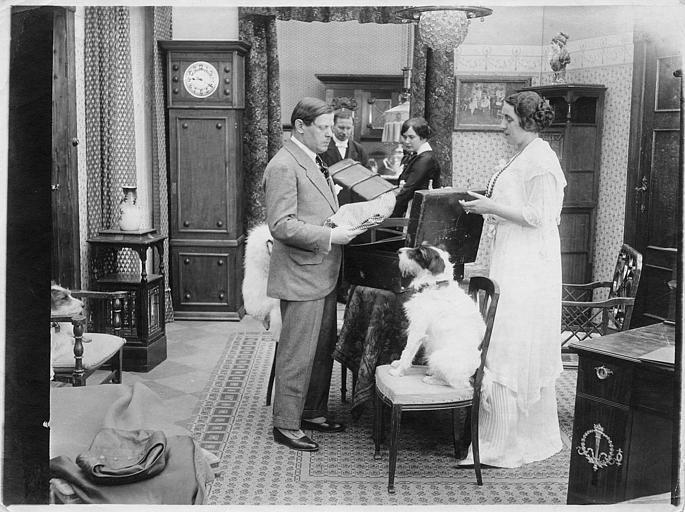 Quatre personnages défaisant des valises et un chien au premier plan