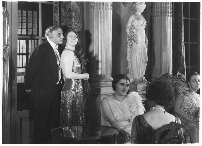 Andrée Lafayette debout dans un salon avec un homme lui respirant les cheveux