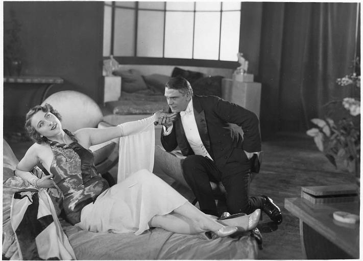 Un homme à genoux baisant la main d'Andrée Lafayette allongée