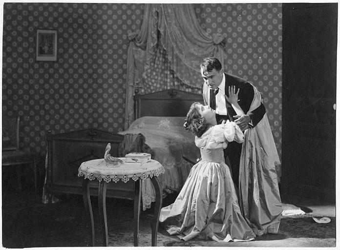 Simone Vaudry à genoux devant Charles Vanel dans une chambre