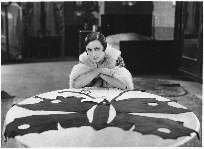 Suzy Pierson dans le rôle Thérèse accoudée sur une table basse ronde dans 'Rue de la Paix' d'Henri Diamant-Berger