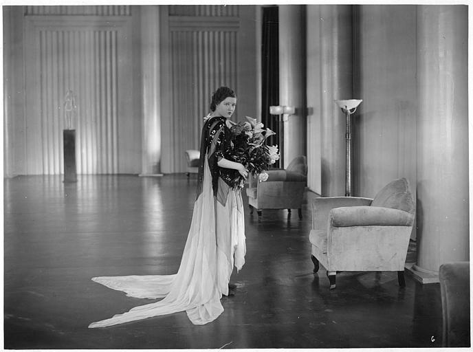 Marie Glory dans le rôle de Line Hamelin portant un bouquet de lys dans une grande pièce dans 'L'argent' de Marcel L'Herbier