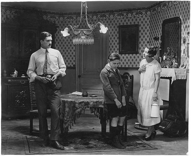 Jean Forest dans le rôle de Gribiche enfant, la tête baissée, entouré de sa gouvernante interprétée par Cécile Guyon et Rolla Norman qui joue Philippe Gavaray dans 'Gribiche' de Jacques Feyder