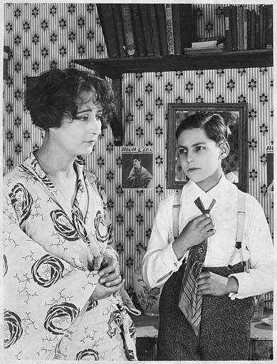 Jean Forest dans le rôle de Gribiche enfant ajustant une cravate dans sa chambre en présence de Cécile Guyon, sa gouvernante, dans 'Gribiche' de Jacques Feyder
