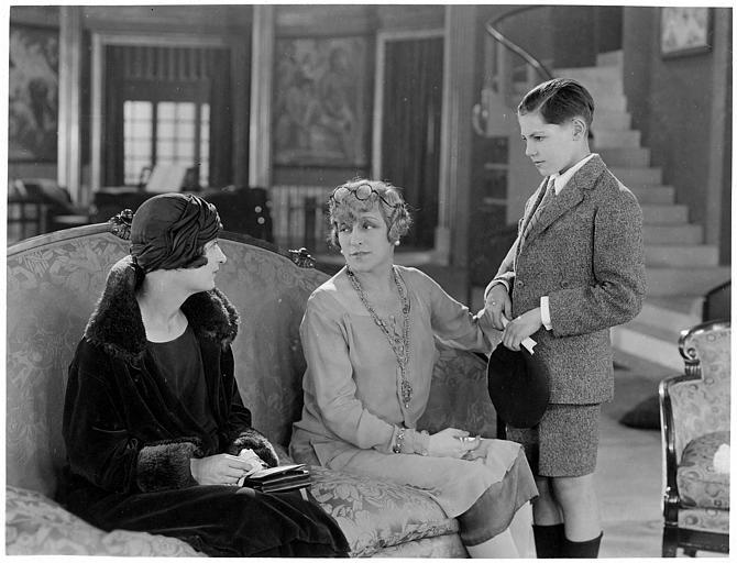 Jean Forest dans le rôle de Gribiche enfant debout à côté de deux femmes assises dans un canapé dans 'Gribiche' de Jacques Feyder