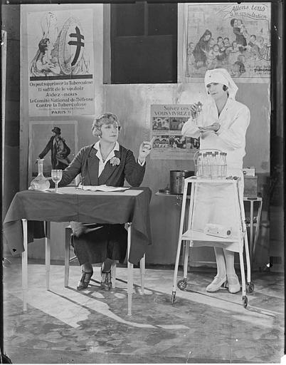Une infirmière présentant des fioles à une femme assise à un bureau avec derrière elles des affiches de prévention médicale dans 'Gribiche' de Jacques Feyder