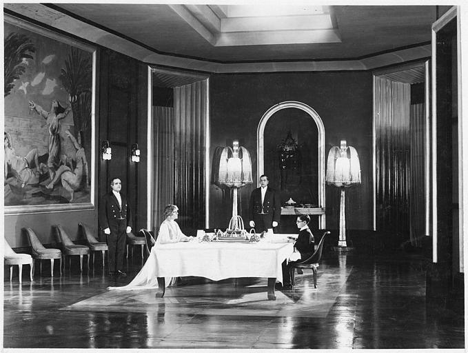 Jean Forest dans le rôle de Gribiche enfant et une femme vêtue richement à table face à face dans une immense salle à manger dans 'Gribiche' de Jacques Feyder