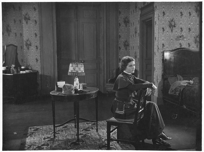 Marie Glory (alias Arlette Genny) dans le rôle de Miss Helyett assise les bras appuyés sur le dossier de sa chaise dans une chambre dans 'Miss Helyett' de Georges Monca