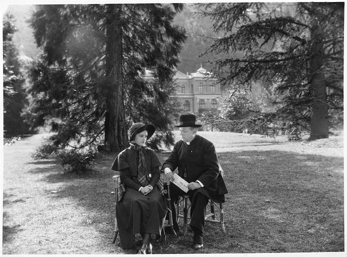 Pierre Hot, qui interprète un pasteur, et Marie Glory (alias Arlette Genny) dans le rôle de Miss Helyett sont assis dans le parc à Vernet-les-Bains dans 'Miss Helyett' de Georges Monca