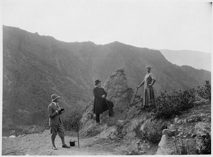 Fernand Fabre, qui joue James Richter, prend en photo Miss Helyett, interprétée par Marie Glory (alias Arlette Genny), qui pose en montagne sous le regard d'un pasteur dans 'Miss Helyett' de Georges Monca