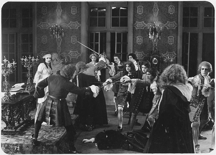 Plusieurs hommes se battent à l'épée au milieu d'un salon et Nilda Duplessy les regarde en arrière plan