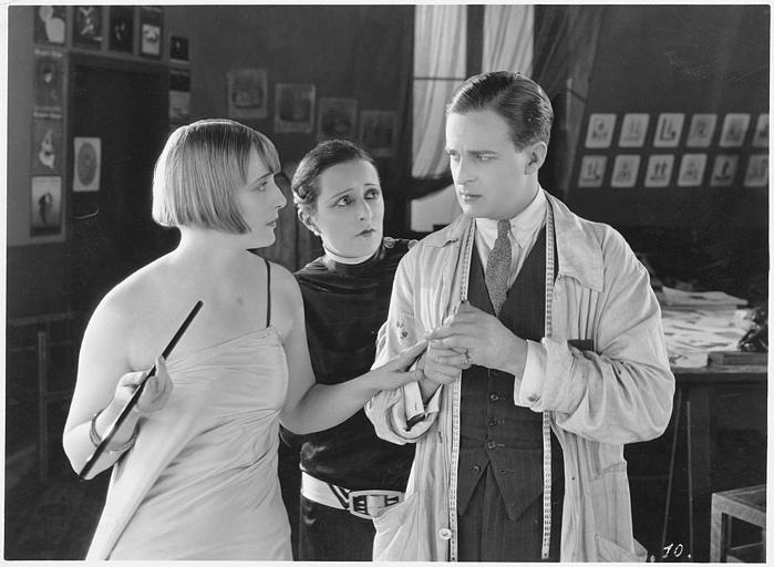 Une femme discute avec un couturier et son assistant en tenant son long fume-cigarette
