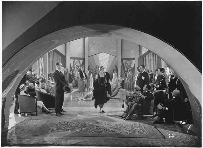 Dans un salon de présentation de modèles de couturier, une femme s'avance devant de nombreux personnages assis la regardant