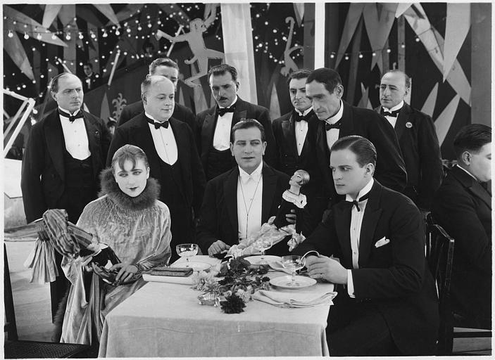 Dans un restaurant, une femme et deux hommes assis à table tiennent des marionnettes avec derrière eux plusieurs hommes en smoking