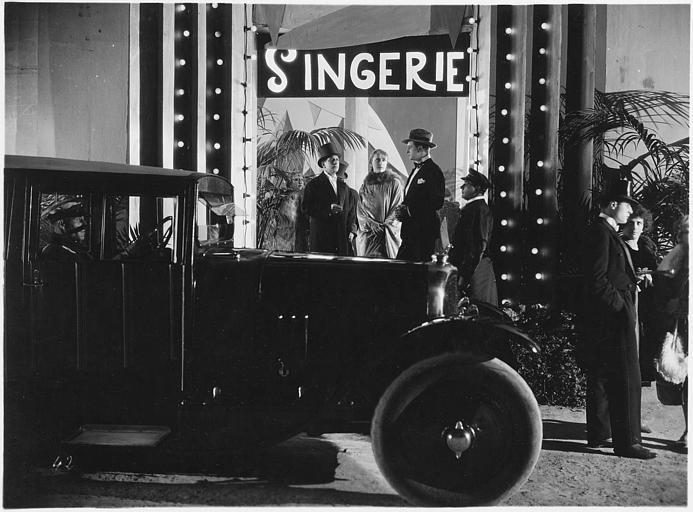 Une voiture et plusieurs personnages devant l'entrée du 'Singerie'