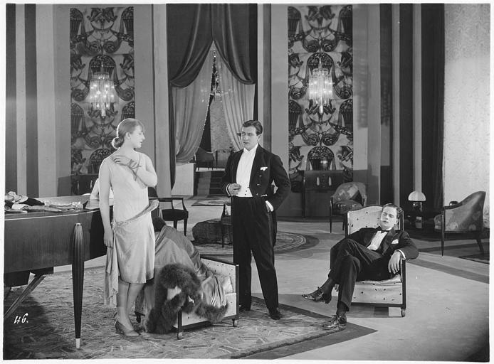 Deux hommes, dont un endormi, et une femme dans une grande pièce avec un piano