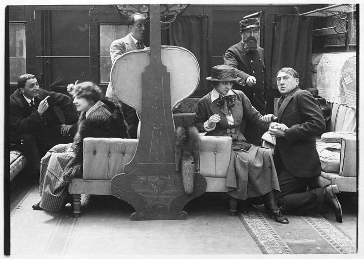 Dans un train, un homme à genoux prenant la main de Jane Renouardt devant le contrôleur dans 'Vous n'avez rien à déclarer?' de Marcel Simon