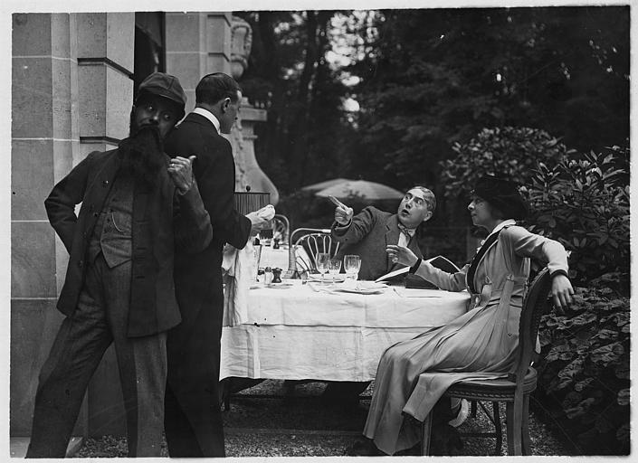 Jane Renouardt et un homme à table sur une terrasse supris par l'arrivée de deux hommes dans 'Vous n'avez rien à déclarer?' de Marcel Simon