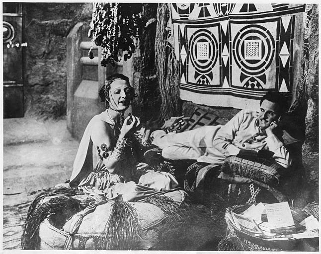 Marie-Louise Iribe dans le rôle de Tanit-Zerga discute avec Georges Melchior qui joue Lieutenant de Saint-Avit en mangeant des confiseries dans un intérieur orientalisant dans 'L'Atlantide' de Jacques Feyder