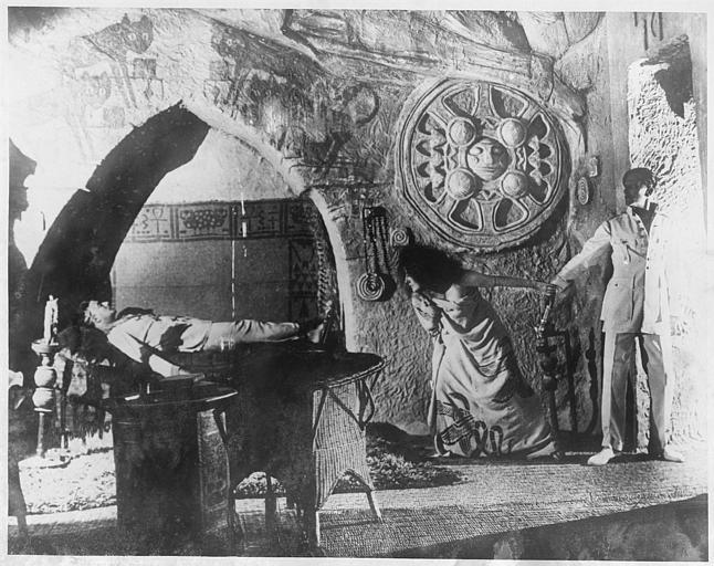 Stacia Napierkowska dans le rôle d'Antinéa et un homme à la sortie d'une pièce dans laquelle un homme est allongé sur un lit dans 'L'Atlantide' de Jacques Feyder