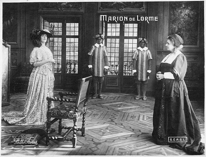 Deux femmes et deux valets dans un salon : Nelly Cormon dans le rôle de Marion dans 'Marion de Lorme' d'Henri Krauss (Pathé)