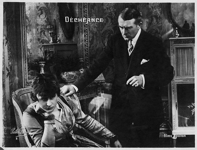 Jeanne Briey assise dans un fauteuil avec Pierre Magnier debout, une main sur son épaule dans 'Déchéance' de Michel Zévaco (Pathé)