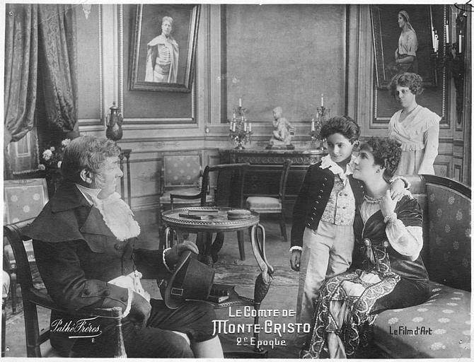 Dans un salon, un homme assis en face d'une femme et son enfant : Nelly Cormon dans le rôle de Mercédès dans le second épisode du 'Comte de Monte-Cristo' d'Henri Pouctal (Pathé)