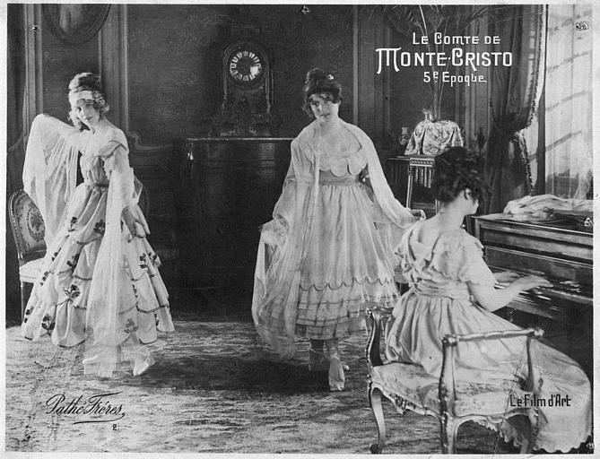Deux femmes dansant dans un salon pendant qu'une troisième joue du piano : Nelly Cormon interprète Mercédès dans le cinquième épisode du 'Comte de Monte-Cristo, 5e époque' d'Henri Pouctal (Pathé)